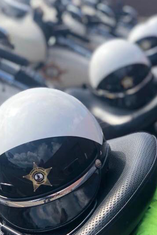 Several officer helmets sitting in a row