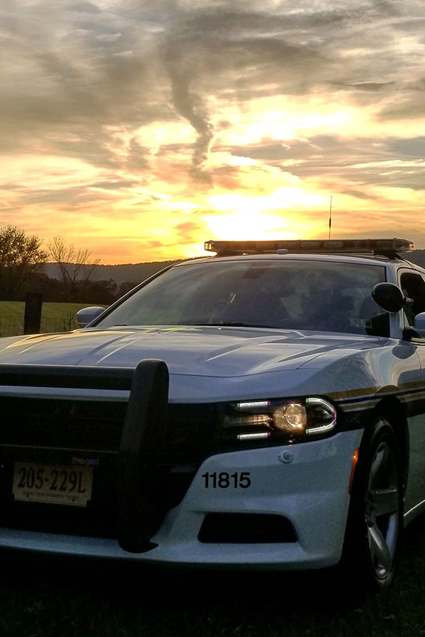 Squad car sitting outside with a sunrise in back