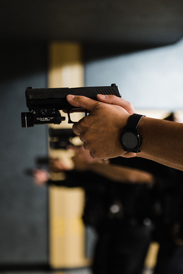 Several officers poised ready to shoot their pistols at a shooting range